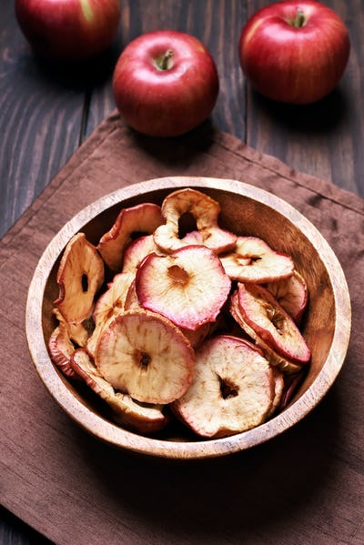 Dehydrated apples chips in wooden bowl