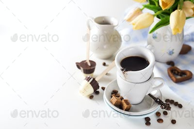 cup of coffee with yellow tulips isolated on white background.