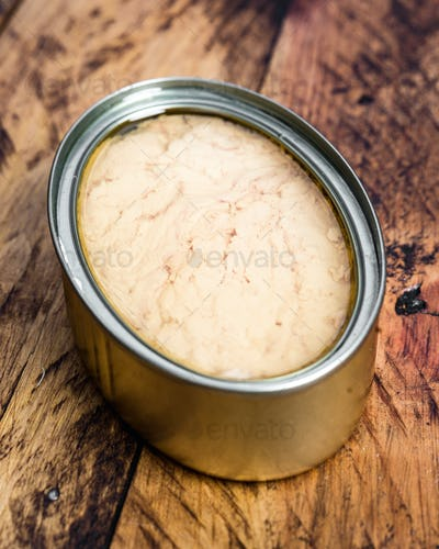tin of metal with pickled tuna, on wooden rustic board