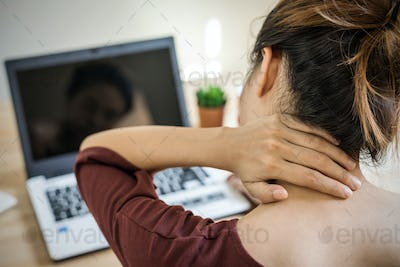 Young woman working at home and having neck pain