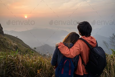 Loving couple embracing on the mountain at sunset.