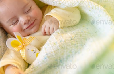 Cute baby sleeping with Easter decorations