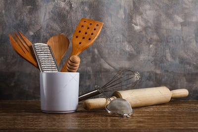 different kitchen utensilson concrete wall background