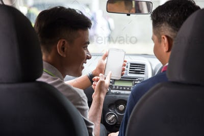 showing his mobile phone to car driver
