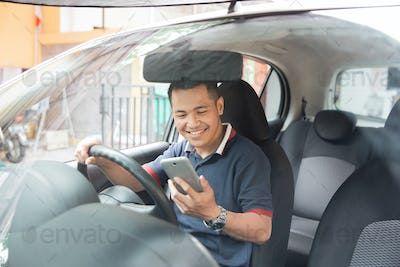 man using smartphone while driving a car