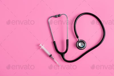 stethoscope and syringe on pink pastel background