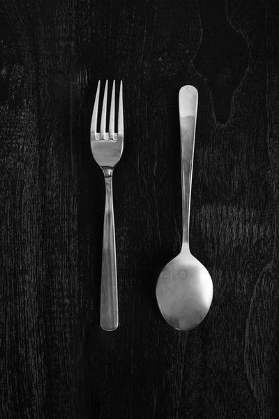 metal fork and spoon on wooden black background