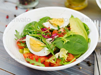 Delicious and light salad of tomatoes, eggs and a mix of lettuce leaves. Healthy breakfast.