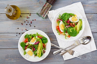 Delicious and light salad of tomatoes, eggs and a mix of lettuce leaves. Healthy breakfast. Top view