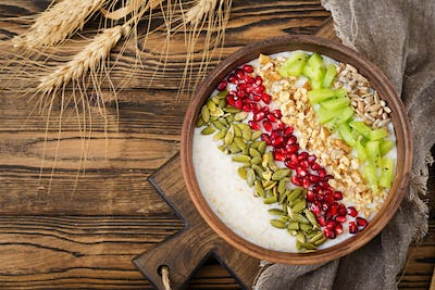 Delicious and healthy oatmeal with kiwi, pomegranate and seeds.
