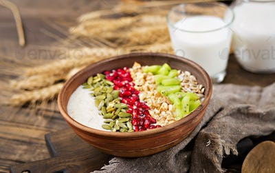 Delicious and healthy oatmeal with kiwi, pomegranate and seeds