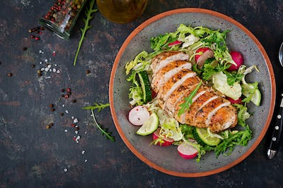 Bowl with salad of fresh vegetables and baked chicken breast on a dark background.