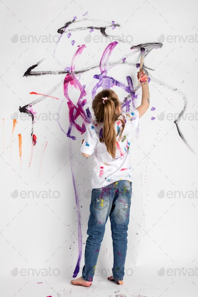 Little girl decorating a white wall with paint