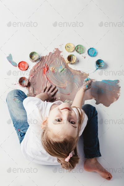 Little girl painting with her hands on the floor.