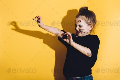 Young child with cat make up streching her hands