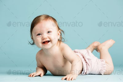 Happy little child crawling on a ground.