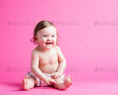 Little kid in a diaper sitting on a pink background