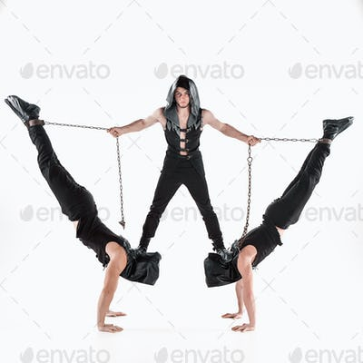 The group of gymnastic acrobatic caucasian men on balance pose