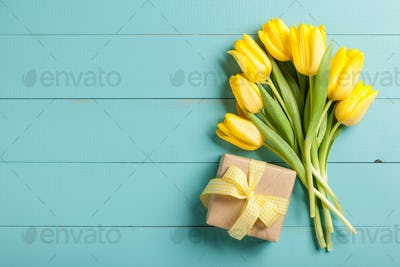 Yellow tulips and gift box on blue wooden background