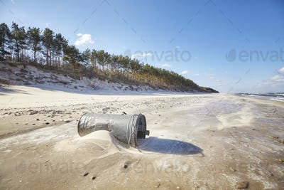 Trash can on a beach, environmental pollution concept