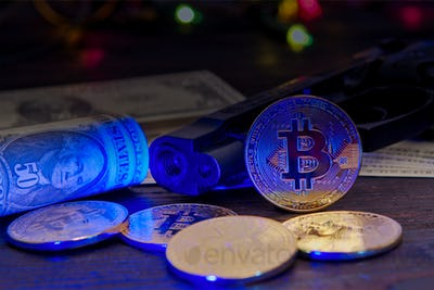 Bitcoins and dollar banknotes on a table with UV light
