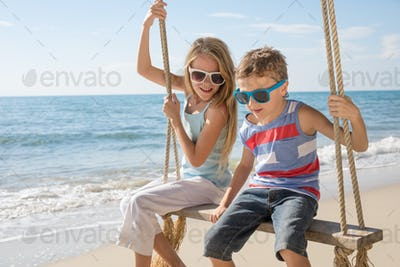 Two happy little children playing on the beach at the day time.