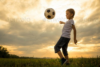Young little boy playing in the field  with soccer ball.