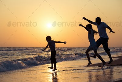 Father son and daughter playing on the beach at the sunset time.