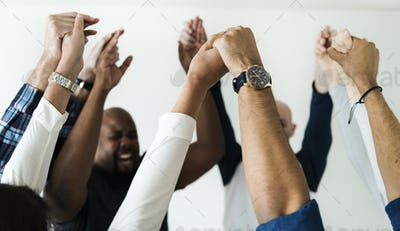 Diverse people joining hands together success and celebration concept