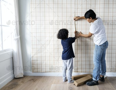 Kid helping mom install wallpaper