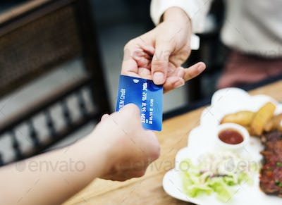 Woman paying lunch with credit card at restaurant
