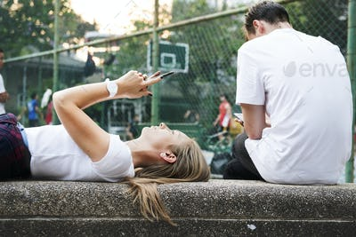 Young woman lying down in the park using a smartphone
