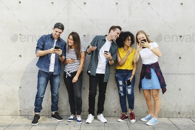 Group of young adults outdoors using smartphones together and ch
