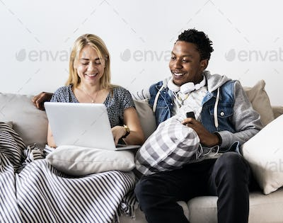 Cute interracial couple on a couch sharing laptop love, internet and music concept