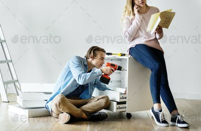 Man using electronic drill install cabinet