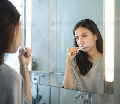 Woman brushing her teeth in the morning