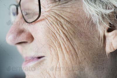 Side closeup portrait of white elderly woman
