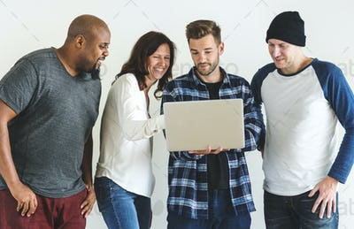 Group of diverse friends using laptop together