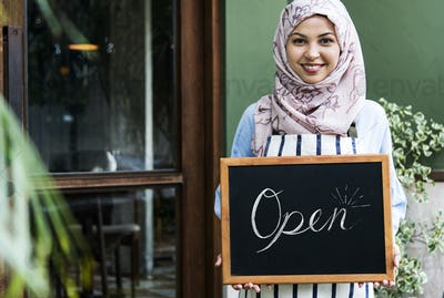 Islamic woman small business owner holding blackboard with smiling