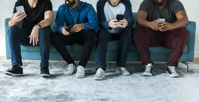 Group of diverse men using mobile phone social media and internet concept