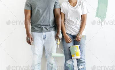 Couple painting house wall