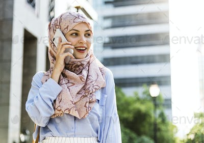 Islamic woman using mobile phone with smiling
