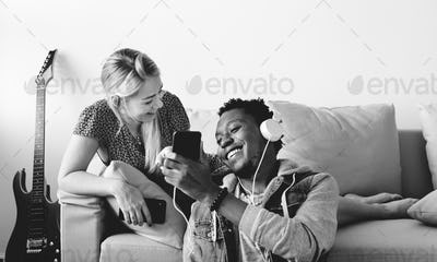 Interracial couple sharing music at home love, leisure and music concept