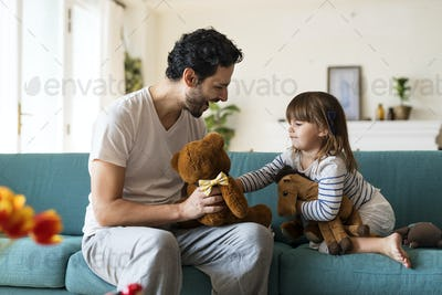 Father playing with his daughter in a living room