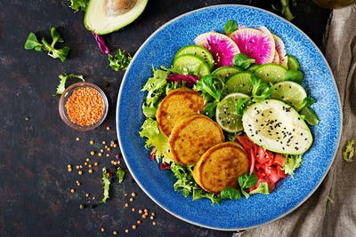 Healthy vegan lunch bowl. Fritter with lentils and radish, avocado salad.