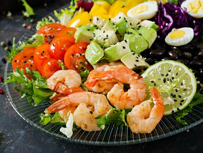 Grilled shrimps and fresh vegetable salad - avocado, tomato, black beans, red cabbage and paprika