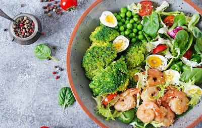 Grilled shrimps and fresh vegetable salad, egg and broccoli. Grilled prawns