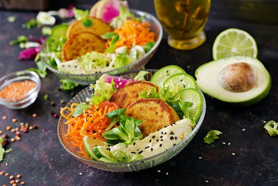 Healthy vegan lunch bowl. Fritter with lentils and radish, avocado, carrot salad.