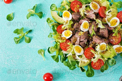 Warm salad from chicken liver, avocado, tomato and quail eggs.