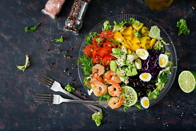 Grilled shrimps and fresh vegetable salad - avocado, tomato, black beans, red cabbage and paprika.
